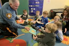 Fall's Township's Officer Yeager giving books to children